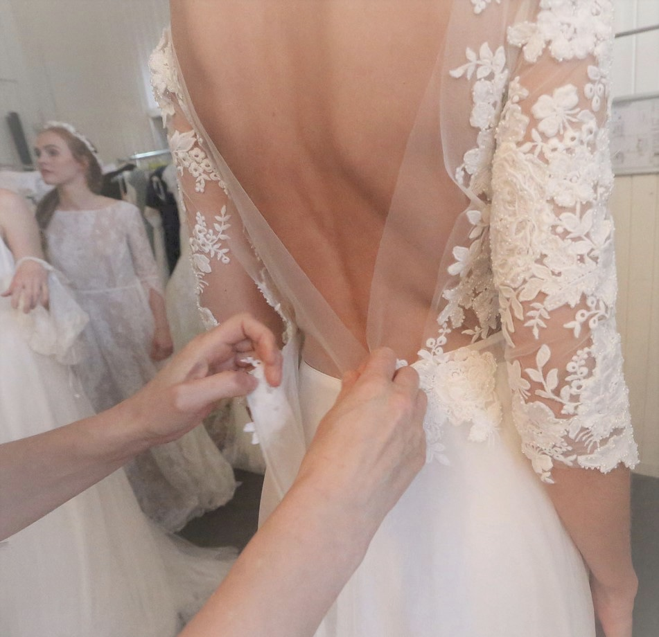Bride during the wedding dress fitting trying to choose the one.